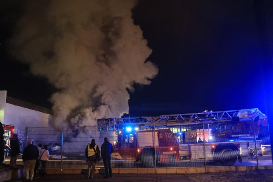 Ein Feuerwehrauto steht am Donnerstagabend vor einem Gebäude einer Druckerei, aus dem Rauch aufsteigt, in Heidenheim. (Archivbild)