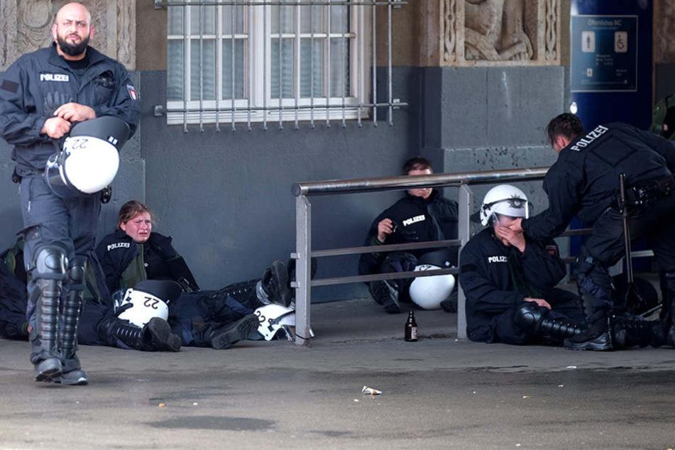 Mit den Nerven am Ende: aufgelöst und erschöpft sitzen die Beamten auf der Straße.
