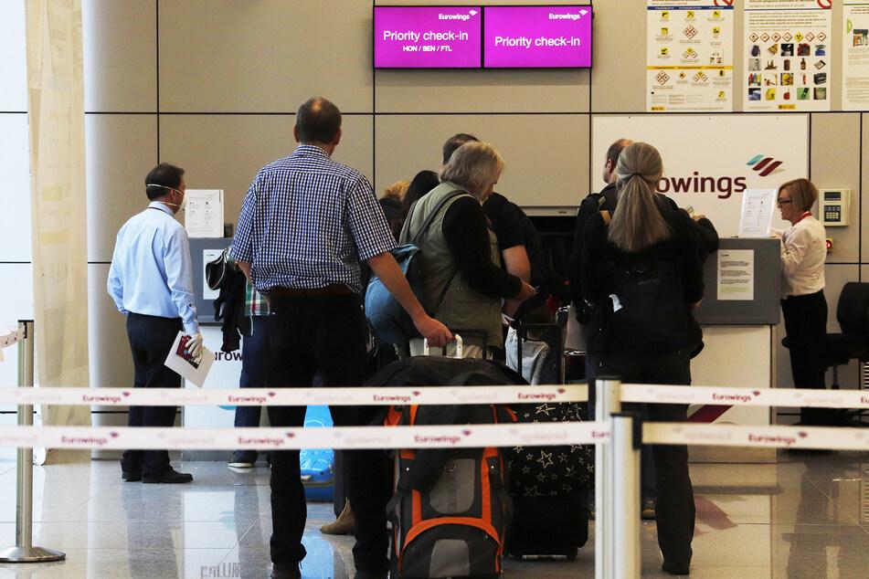 Passagiere warten am Flughafen von Palma de Mallorca vor einem Check-in-Schalter von Eurowings. (Symbolbild)