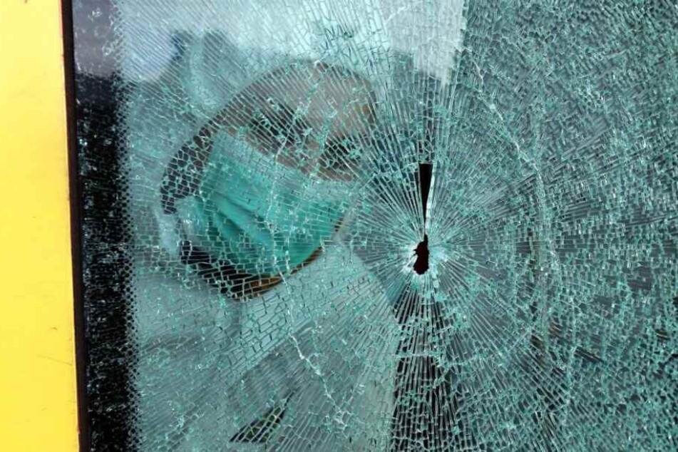Erneut begutachten Ermittler eine kaputte Scheibe an einer Stadtbahn.