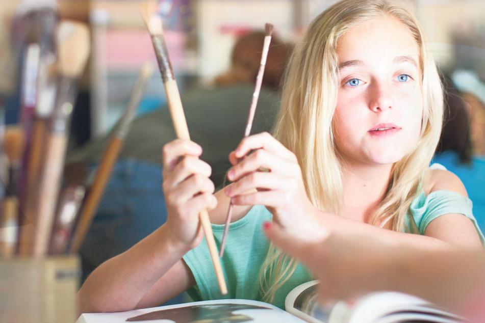 Dicker oder dünner Pinsel? Dieses Schulmädchen kann sich nicht entscheiden. Beim Malen lernen Kinder, ihren Ideen Farbe und Form zu geben.