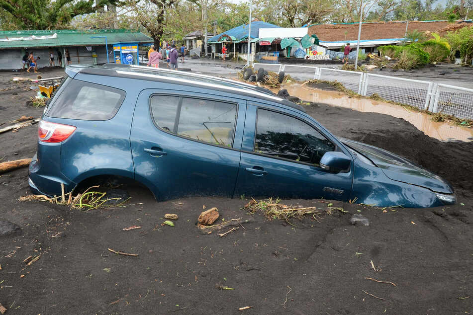 A car is buried in mud after a flood brought by the heavy rains from typhoon Goni in Albay Province, the Philippines.