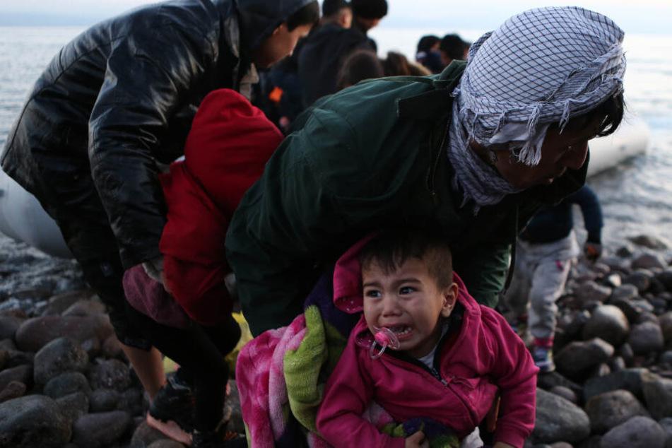 Flüchtlinge und Migranten verlassen nach ihrer Ankunft auf der griechischen Insel Lesbos ein Boot.