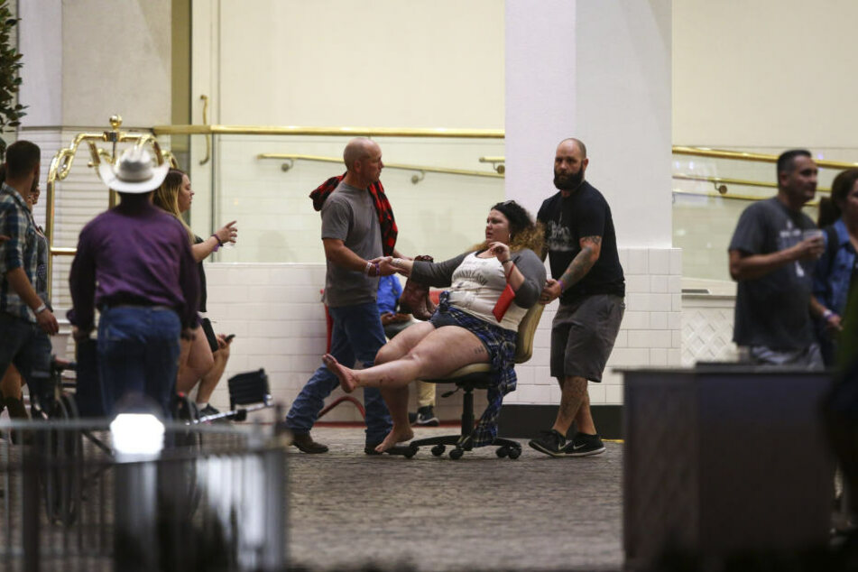 Zwei Männer helfen nach der Tat einer verletzten Frau.