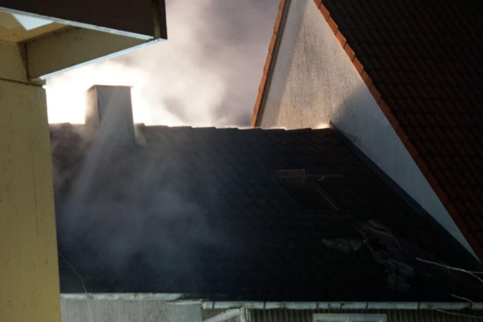 Qualm dringt aus dem Dach des Hauses.
