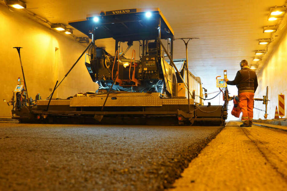 Arbeiter im Schwanenplatztunnel tragen neuen Fahrbahnbelag auf.