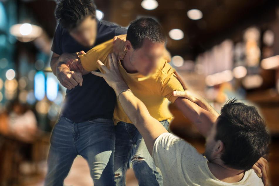 Männer greifen Kneipengäste an und schlagen sie zu Boden