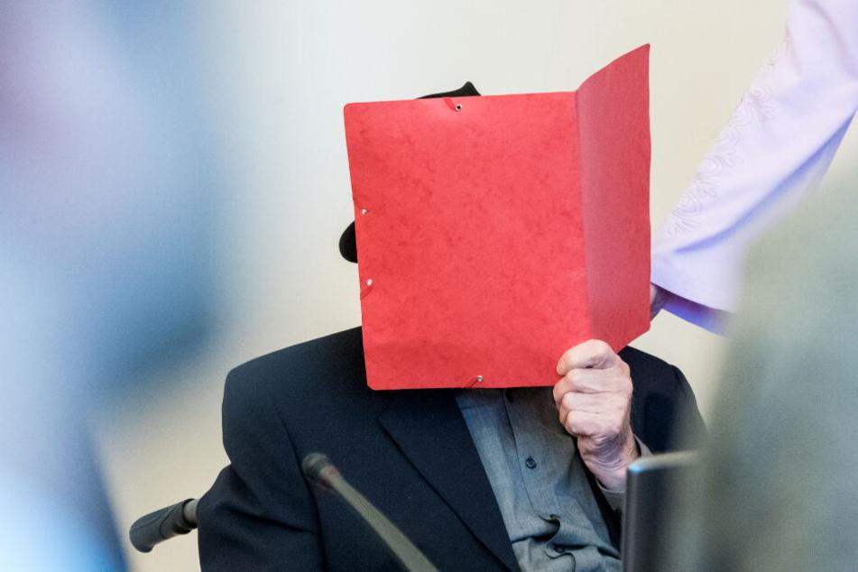 Der Angeklagte verbirgt sein Gesicht hinter einem Aktenordner.