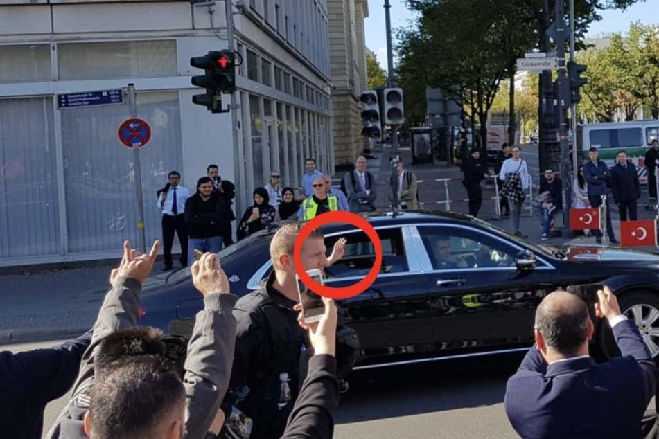 """Erdogan im Mercedes-Maybach zeigt mit vier Fingern den islamistischen Gruß (Kreis). Seine Anhänger grüßen mit der """"Wolfsschnauze"""" zurück."""