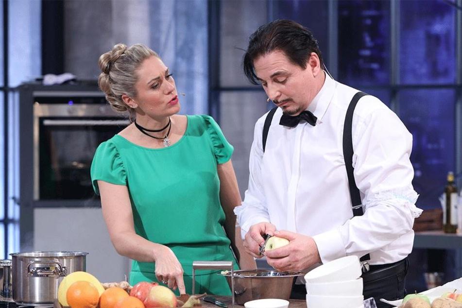"""Für den Nachtisch schält Brautmodenprofi Uwe Herrmann (55) Äpfel. """"Grill den Profi""""-Moderatorin Ruth Moschner (42) schaut ihm genau auf die Finger."""