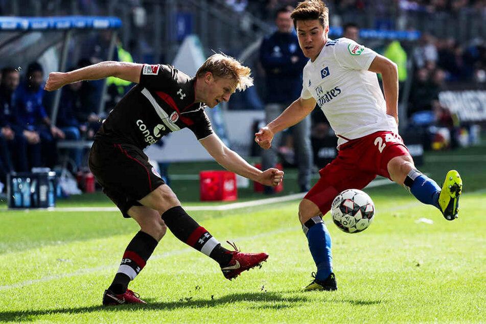 St. Paulis Mats Möller Daehli (l.) klärt den Ball vor HSV-Akteur Gotoku Sakai (r.).