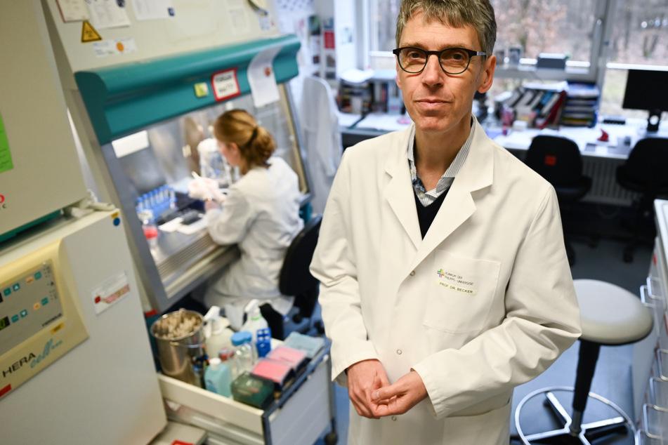 Professor Stephan Becker (r), Direktor des Instituts für Virologie der Philipps-Universität Marburg, steht in einem Forschungslabor neben einer Sterilwerkbank.