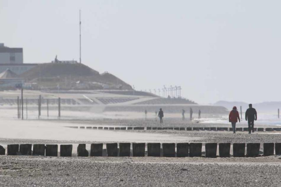 Nur vereinzelt gehen Menschen am Strand von Norderney spazieren.