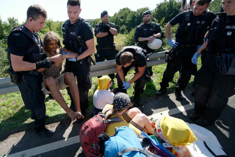 """Polizisten tragen ein Mitglied der Aktionsgruppe """"Kohle erSetzen!"""", die eine Straße blockieren, die zum Braunkohletagebau Garzweiler führt."""
