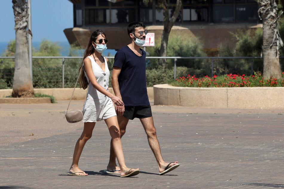 Passanten tragen Mundschutze, während sie auf einer Straße gehen.