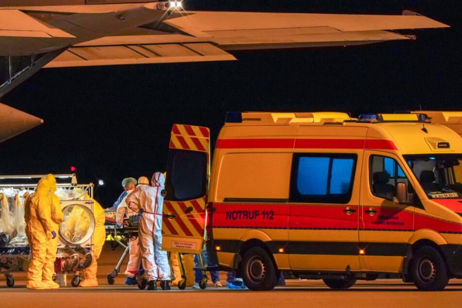 Die Patienten werden aus dem Militärflugzeug in die Krankenwagen verlegt.