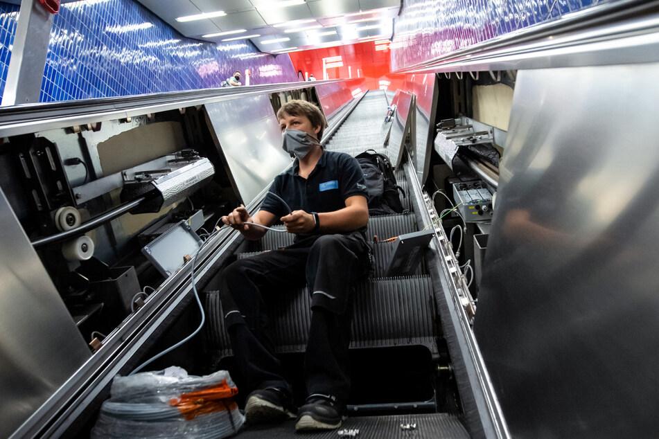 Christian Hacker, Mitarbeiter von den Stadtwerken München, installiert an einer Rolltreppe im S- und U-Bahnhof Marienplatz UV-Lampen.