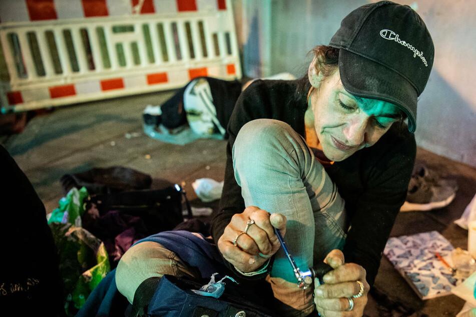 Eine 44-jährige Drogenabhängige zündet sich auf einem Gehweg im Frankfurter Bahnhofsviertel ihre Crackpfeife an.