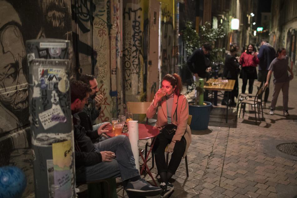 Frankreich, Marseille: Freunde trinken ein Getränk vor einer Bar vor der Ausgangssperre.