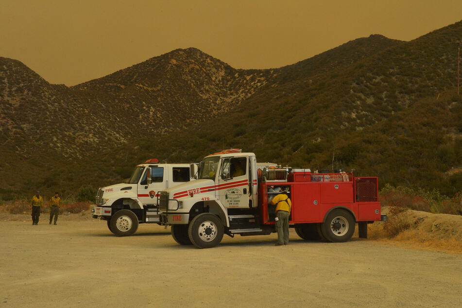 September, 21, 2020: firefighters rest on the Angeles Crest Highway as smoke from the Bobcat Fire envelops the San Gabriel Mountains in Juniper Hills, California.