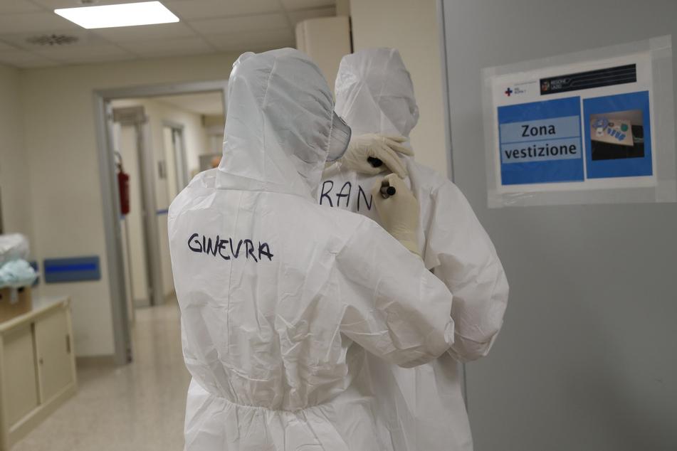 Die Krankenschwestern Ginevra Fattori (l) und Francesca Tulli schreiben ihren Namen auf ihre Schutzanzüge vor ihrer Schicht in der Intensivstation des Krankenhaus San Filippo Neri.