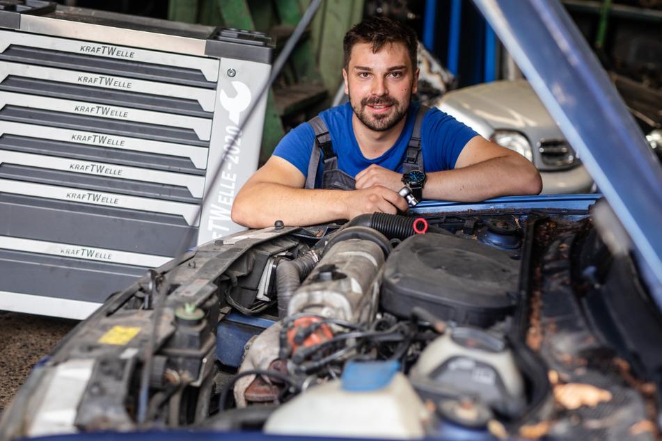 Wolfgang Richard Resch (24) arbeitet in einer Werkstatt auf dem Gelände der Autoverwertung Resch an einem Auto.