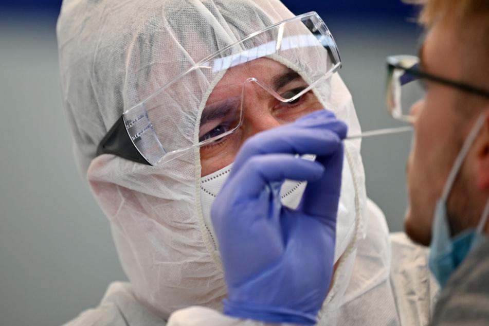 Ein Helfer entnimmt eine Probe für einen Corona-Schnelltest.