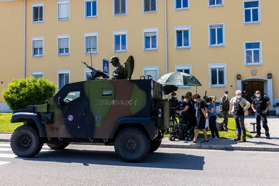 Ein Filmteam des SWR baut eine Einstellung auf, während im Vordergrund ein französisches Militärfahrzeug zu sehen ist.