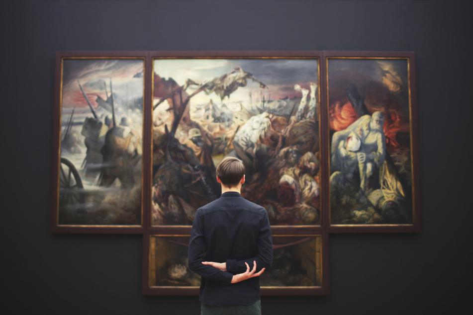 Mann beobachtet Gemälde. (Foto: Igor Miske, Unsplash)