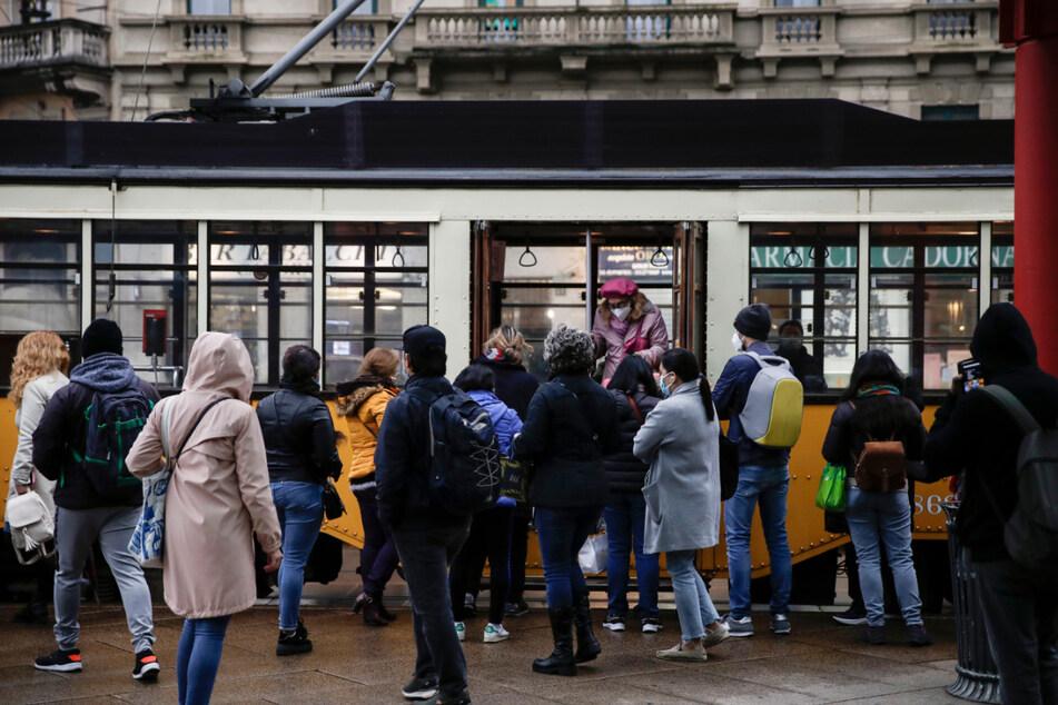 """Menschen warten in Mailand, bis sie in die stehende Straßenbahn einsteigen können. Italienische Gesundheitsbehörden erklärten, das Land sei in einer """"akuten Phase"""", nachdem die Fälle der Corona-Infektionen wieder besorgniserregend steigen."""