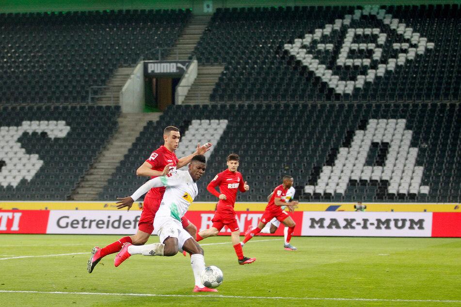 Der Mönchengladbacher Breel Embolo (r) und der Kölner Ellyes Skhiri kämpfen in dem leeren Stadion um den Ball.