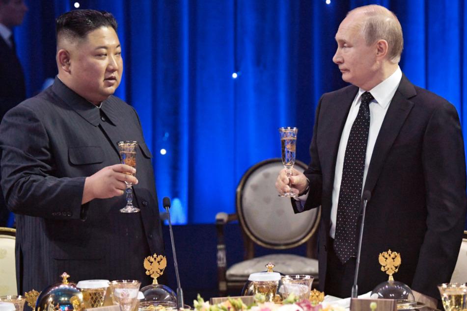 Kim Jong Un (l.), Machthaber von Nordkorea, und Wladimir Putin, Präsident von Russland, stoßen nach einem Gespräch miteinander an. (Archivbild)