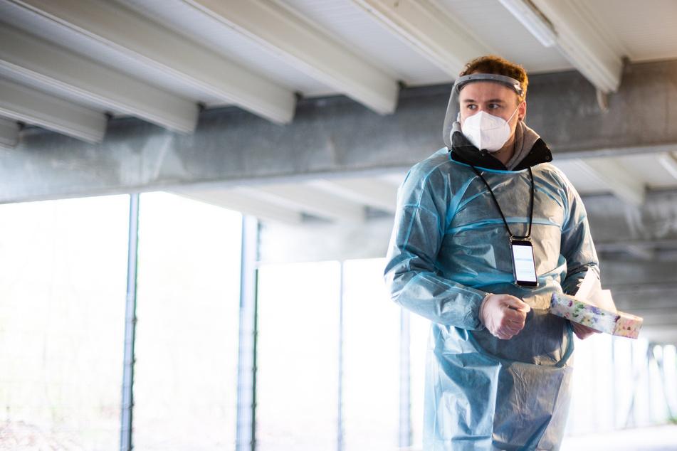 Ein Helfer steht mit Taschentücher zum Nase schnäuzen für Corona-Schnelltests in einem Testzentrum.