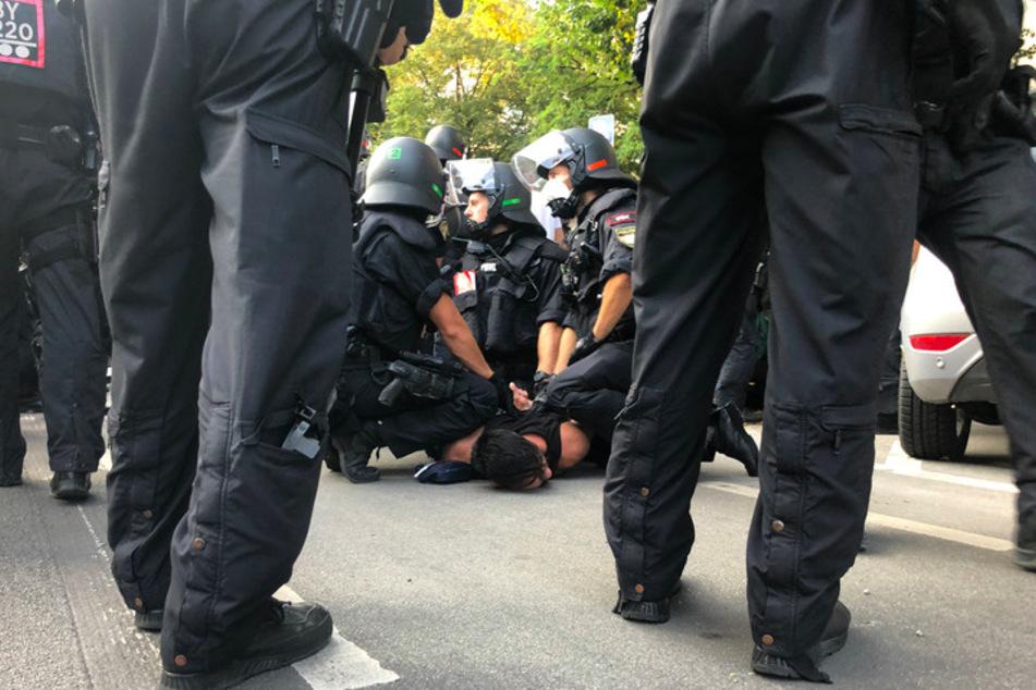 Polizisten nehmen neben der Theresienwiese bei einer Demonstration gegen die Corona-Maßnahmen einen Mann fest.