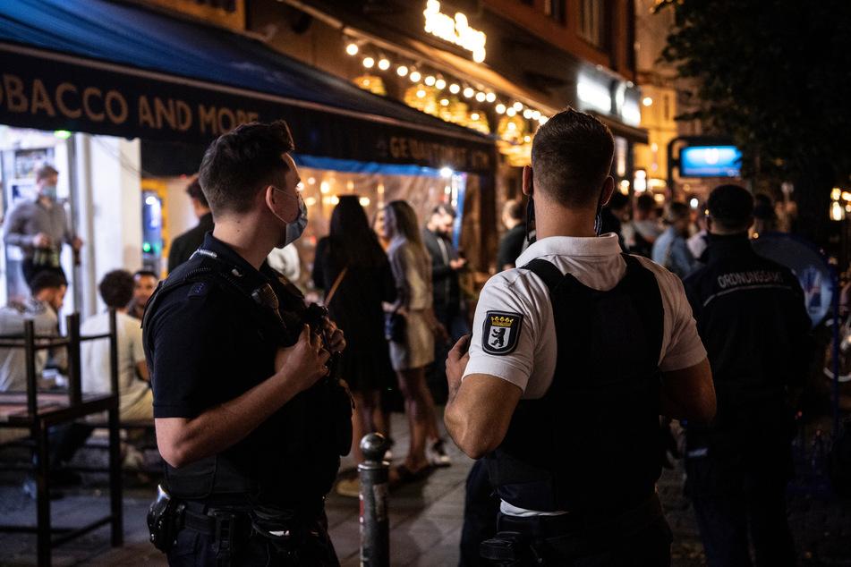 Ein Polizeibeamter und ein Mitarbeiter des Ordnungsamtes stehen vor einem Lokal.