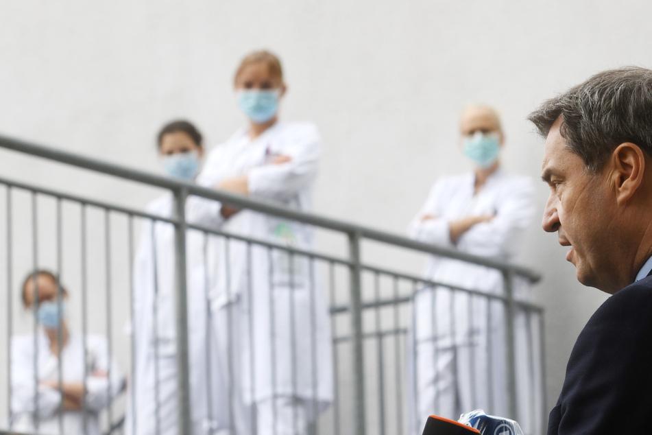 Klinikpersonal verfolgt die Äußerungen von Markus Söder (CSU,r), Ministerpräsident von Bayern, nach einem Besuch der Intensivstation in der München Klinik Schwabing. Ministerpräsident Söder und Oberbürgermeister Reiter hatten die Covid-19-Intensivstation in Haus 3 besucht.