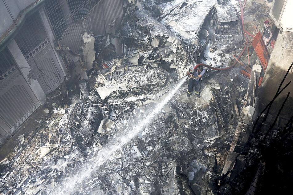 Ein Feuerwehrmann versucht, das Feuer an der Absturzstelle zu löschen.