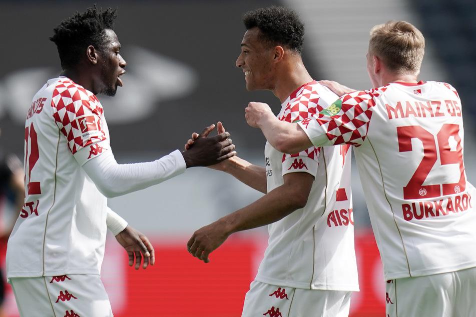 Die Mainzer Danny da Costa (l.) und Jonathan Burkardt (r.) bejubeln den Treffer von Karim Onisiwo zum 1:0 gegen Eintracht Frankfurt.