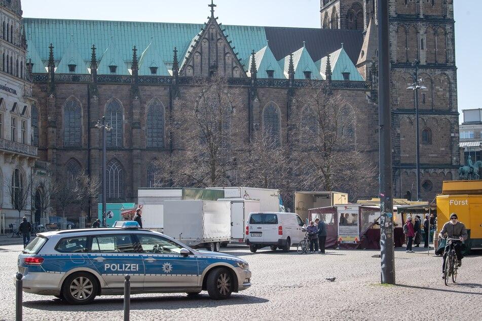 Polizei fährt an einem Wochenmarkt neben dem Bremer Dom vorbei, um das Kontaktverbot zu kontrollieren, das verhängt worden ist um die Ausbreitung des Coronavirus einzudämmen.
