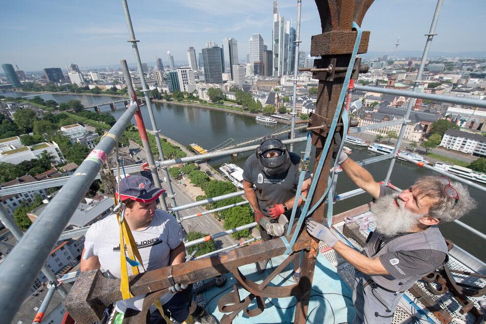 Vor der Hochhauskulisse von Frankfurt arbeiten Maurer Jonas Kirchner, Metallbauer David Pößel und Steinmetz Reinhart Vierkant (v.l.n.r.) an der Demontage des Kreuzes auf dem Turm der Dreikönigskirche am Mainufer.