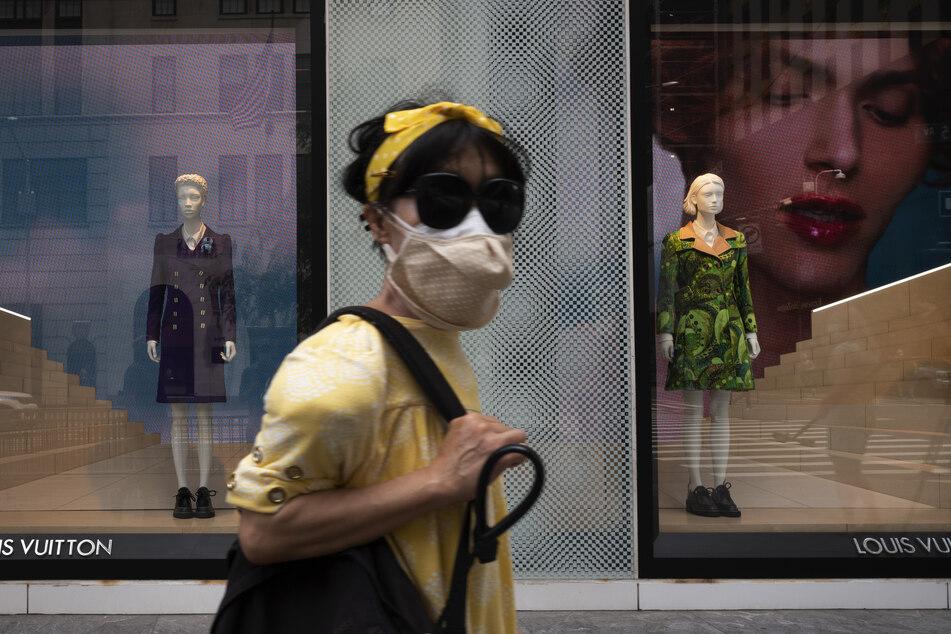Eine Frau mit Mundschutz geht an einem Louis Vuitton-Geschäft im New Yorker Einkaufsviertel Fifth Avenue vorbei. Das Luxusgütergeschäft ist zur Abholung am Straßenrand geöffnet.