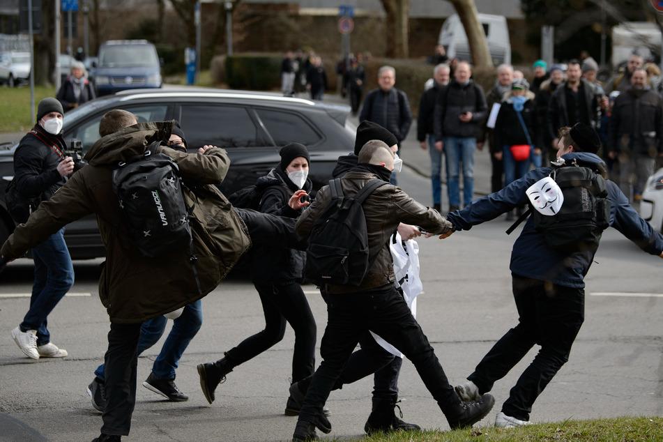 Anhänger der Querdenker-Bewegung versuchen einem Gegendemonstranten ein Banner zu entreißen. Ein Fotograf, der die Szene dokumentierte, soll daraufhin einen Faustschlag ins Gesicht erhalten haben.
