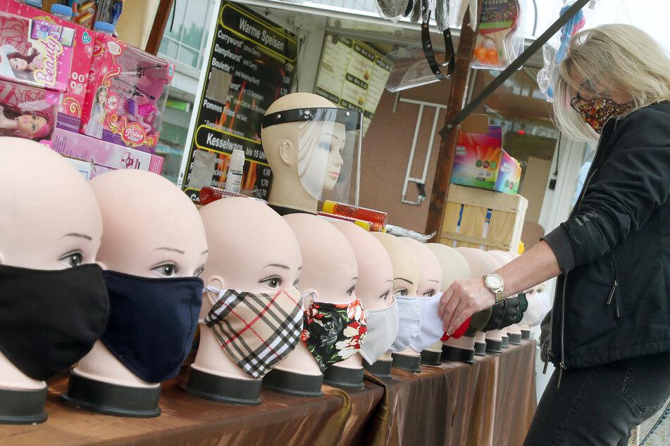 Eine Frau mit Mund-Nasen-Schutz betrachtet auf einem Wochenmarkt handgefertigte Schutzmasken, die zum Kauf angeboten werden. (Archivbild)
