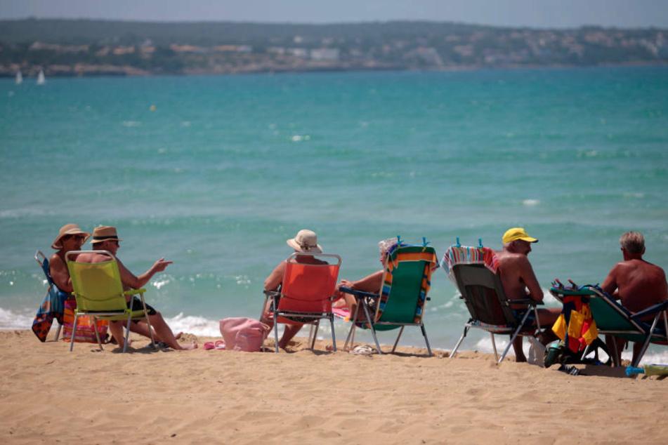 Badegäste sitzen am Strand von Palma de Mallorca. Nach wochenlanger Corona-Pause ist am Montagvormittag erstmals wieder eine Maschine mit Urlaubern aus Deutschland in Mallorca gelandet.