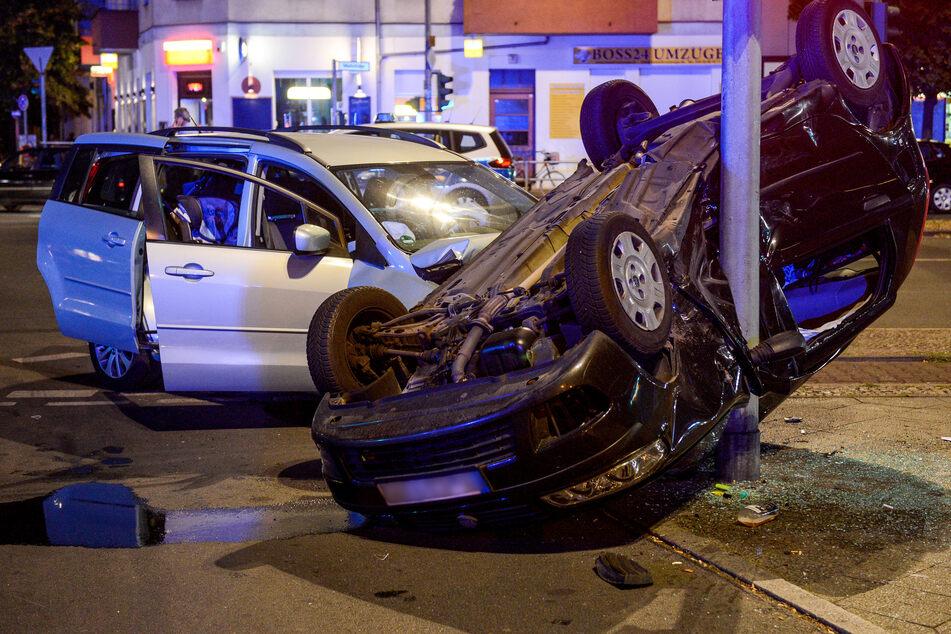 Unfall Berlin - dunkles Auto überschlagen und Kollision mit Laternenmast an Berliner Kreuzung.