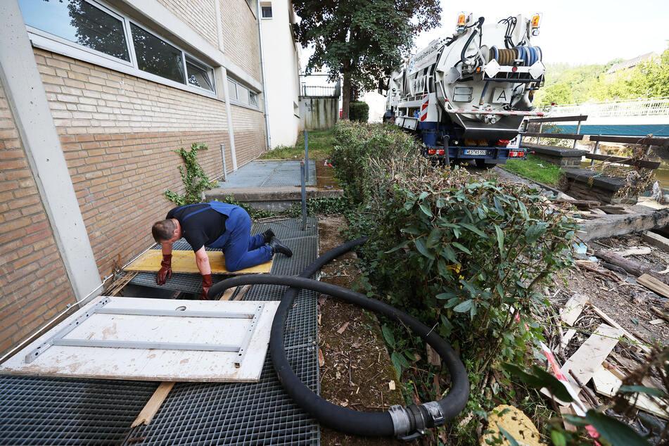 Ein Mitarbeiter des Spezialentsorgers der KS-Recycling GmbH hält an einer Schule in Schleiden einen Schlauch zum Abpumpen des Wassers in den Keller.