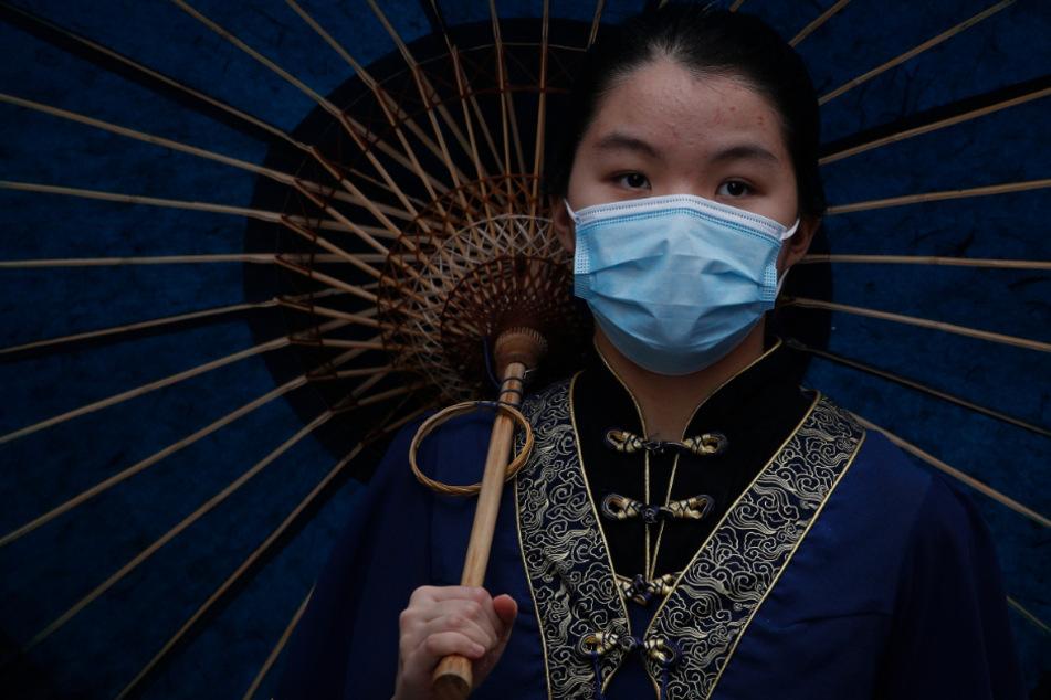 China, Peking: Eine Frau in traditioneller Tracht trägt eine Mundschutzmaske und hält einen Schirm.