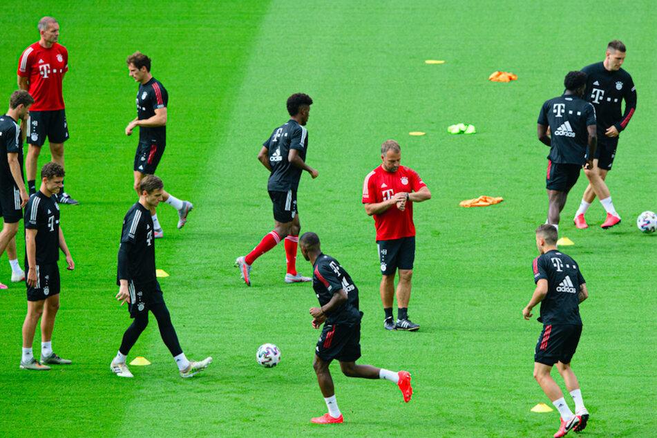Bayern Münchens Trainer Hansi Flick (M) schaut beim Training im Olympiastadion inmitten seiner Spieler auf die Uhr.