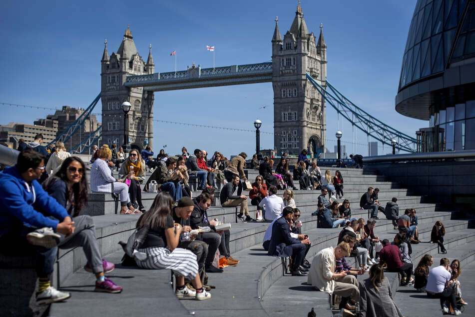 Zahlreiche Menschen sitzen bei gutem Wetter in der Nähe der Tower Bridge in London auf Treppenstufen. Großbritannien kommt im Kampf gegen das Coronavirus gut voran, zahlreiche Menschen sind bereits geimpft.