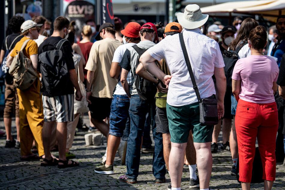 Menschen warten in der Schlange eines mobilen Impfteams auf dem Hermannplatz.
